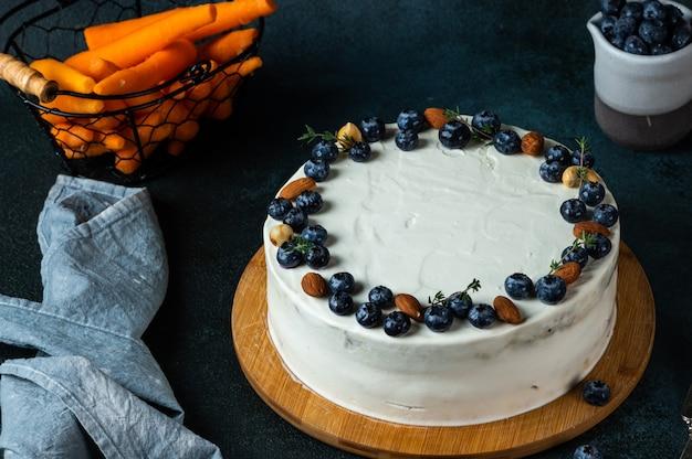 Karottenkuchen mit walnüssen und blaubeere auf dunklem hintergrund. lokales essen. traditioneller amerikanischer kuchen. kuchen zum erntedankfest. herbstkuchen.