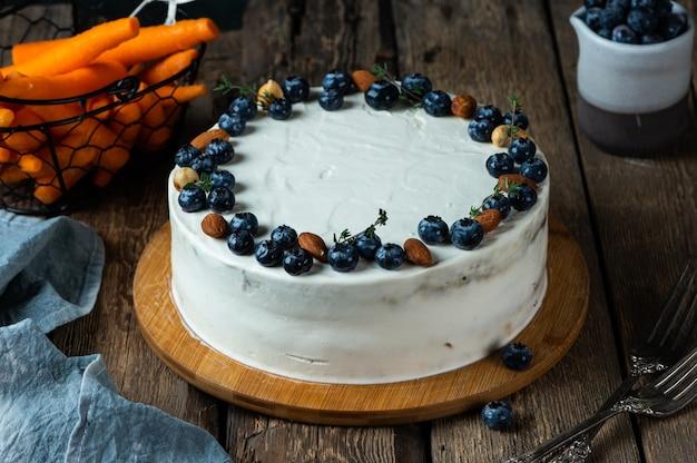 Karottenkuchen mit walnüssen und blaubeeren auf dunklem holzhintergrund lokale küche traditioneller amerikanischer kuchen