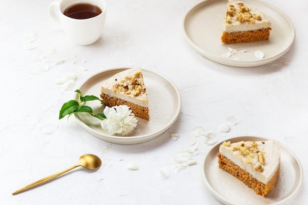 Karottenkuchenstücke mit kokoscreme und walnüssen auf tellern zuckerfrei, gluten- und laktosefrei