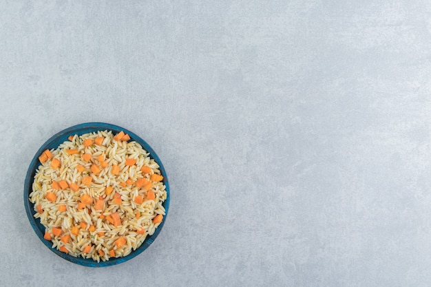 Karottenreis in der holzplatte, auf dem marmorhintergrund.