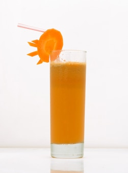Karottensaft in einem glas mit einem strohhalm und einer karottenscheibe. getränk isoliert auf weißem hintergrund