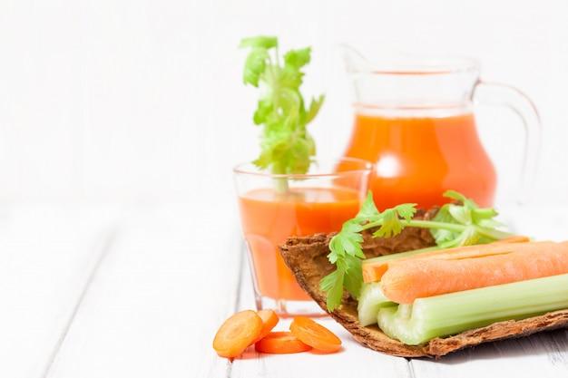 Karottensaft in schönen gläsern, geschnittene karotte und grüner sellerie auf hölzerner rindenschüssel