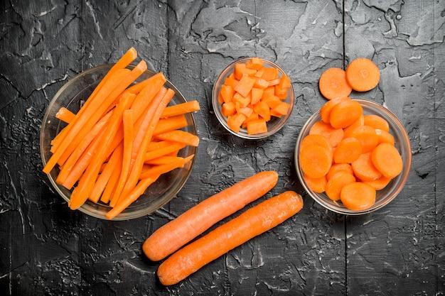 Karottenstücke auf einer schüssel. auf schwarzem rustikalem hintergrund