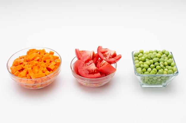 Karottentomate und erbse zur herstellung von rotem reis in glasbehältern mit weißem hintergrund