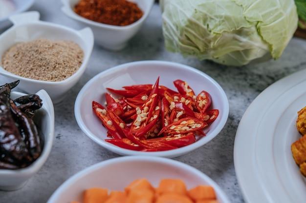 Karottenwürfel, getrocknete chilis, gerösteter reis, chili und kohl werden auf einen zementboden gelegt