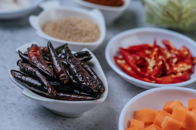 Karottenwürfel, getrocknete chilis, gerösteter reis und chilipaste auf einem zementboden.