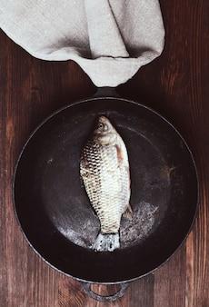Karpfen der frischen fische in einer schwarzen bratpfanne