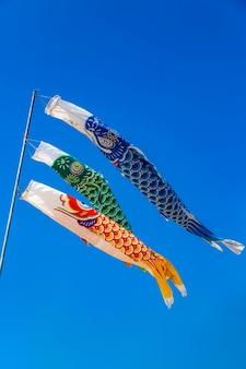 Karpfenförmige bunte windsäcke gegen klaren blauen himmel