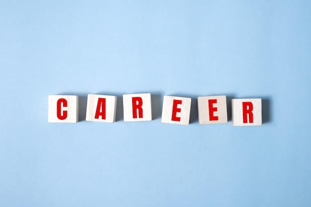 Karriereberater, der das wort karriere mit holzwürfeln in einem konzeptuellen bild persönlicher führung zur selbstverwirklichung zusammenfügt.