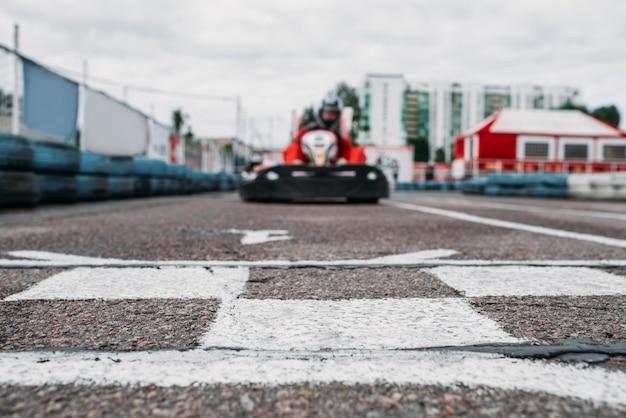 Kart-rennfahrer auf der ziellinie, go-kart-wettbewerb