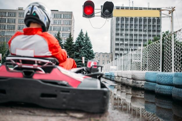 Kart-rennfahrer, go-kart-fahrer an der startlinie, rückansicht. carting speed trac, extremer motorsport