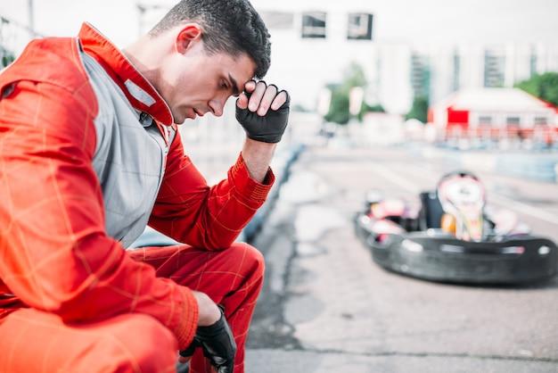 Kart-rennfahrer sitzt auf einer reifen-outdoor-kartbahn