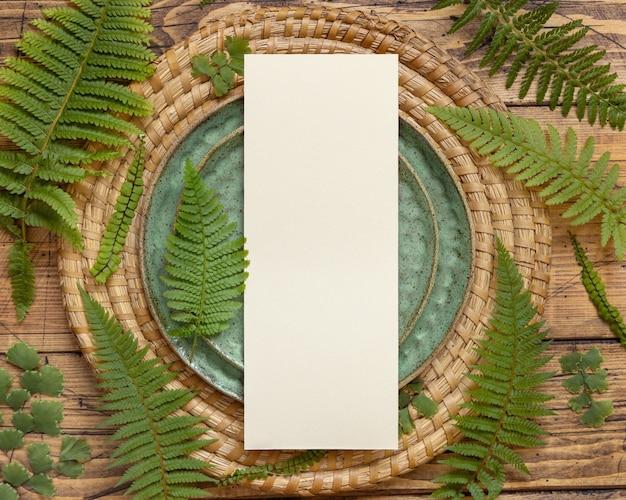 Karte des leeren papiers, die auf grünem teller auf braunem holztisch mit draufsicht der farnblätter legt. tropische mock-up-szene mit flacher einladungskarte