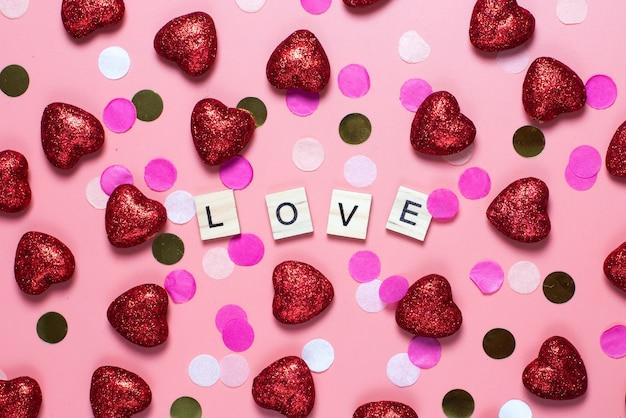 Karte für valentinstag. auf einem rosa hintergrund holzbuchstaben mit liebe ausgekleidet. lustige glückwünsche. flache lage, draufsicht.