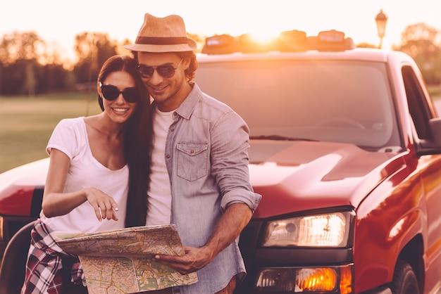 Karte gemeinsam untersuchen. schönes junges paar, das sich aneinander bindet und sich an ihren pick-up-truck lehnt, während es gemeinsam die karte untersucht