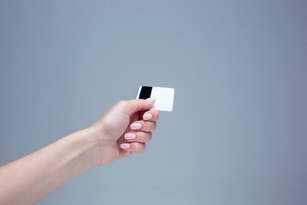 Karte in einer weiblichen hand ist auf einem grauen hintergrund
