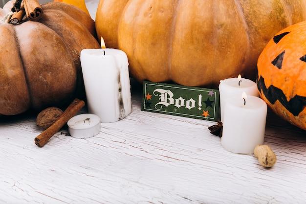 Karte mit dem schriftzug 'boo' steht vor scary halloween kürbisse