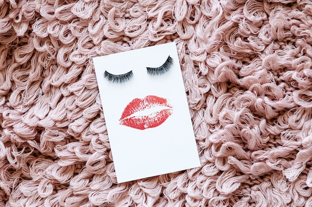 Karte mit falschen wimpern und rotem kuss auf rosa fell