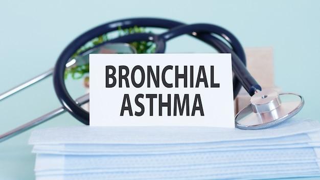 Karte mit worten asthma bronchiale, stethoskop, gesichtsmasken und blume auf tisch auf tisch.