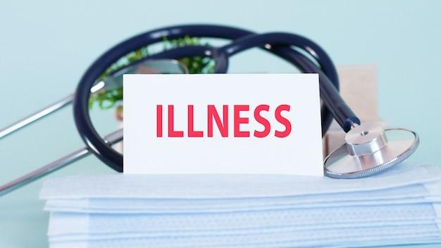 Karte mit worten krankheit, stethoskop, gesichtsmasken und blume auf dem tisch auf dem tisch. persönliche schutzausrüstung auf weichem blauem hintergrund. medizin- und gesundheitskonzept.