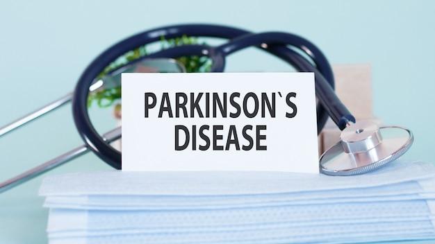 Karte mit worten parkinsons krankheit, stethoskop, gesichtsmasken und blume auf tisch auf tisch