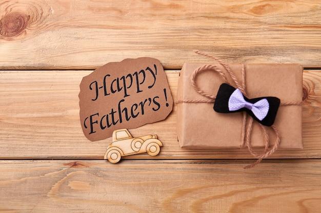 Karte und geschenk des glücklichen vaters. brandmalerei-auto in der nähe von fliege. papa wird dein bemühen zu schätzen wissen.