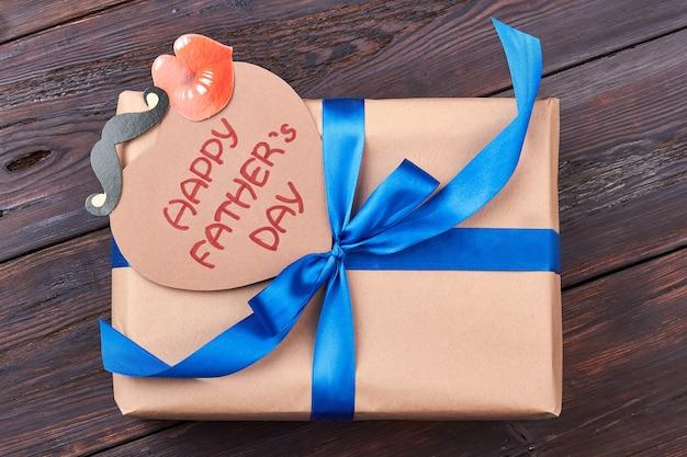 Karte und geschenk für vater. geschenkbox auf holzhintergrund. unterstütze deinen vater.