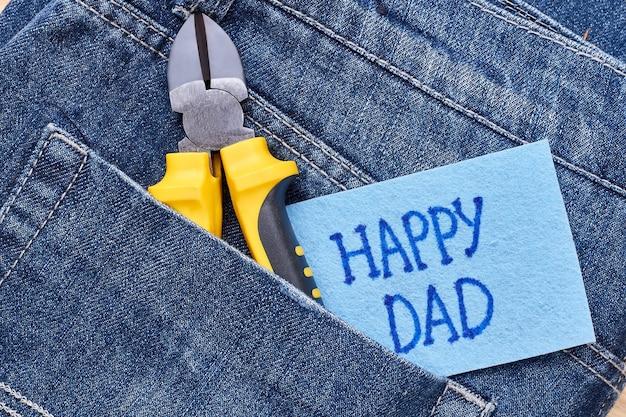 Karte und zange des glücklichen vaters. grußkarte auf jeanstasche. überrasche deinen vater.