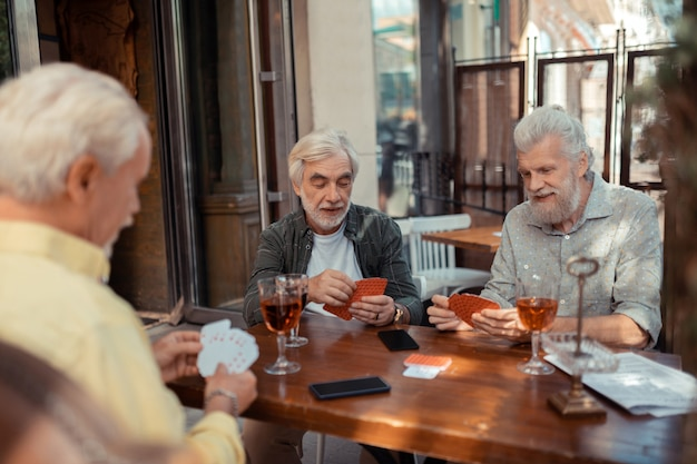Karten und alkohol. drei männer im ruhestand, die draußen karten spielen und alkohol trinken drinking