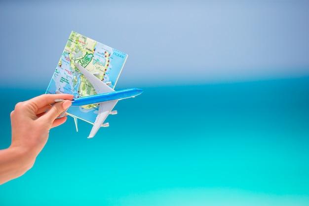 Karten- und spielzeugflugzeug das türkisfarbene meer