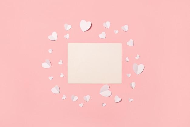 Karten- und weißbuchherzen auf einem rosa hintergrund. zusammensetzung valentinstag. banner. flache lage, draufsicht.