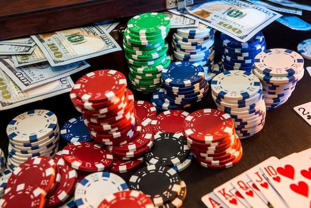Kartenchips und geld auf dem schwarzen tisch.
