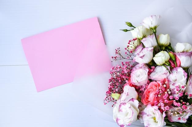 Kartenmodell mit zartem blumenstrauß. blumenhintergrund. draufsicht flache laien-feiertagskarte 8. märz, glücklicher valentinstag, muttertagskonzept. kopieren sie platz für text. feiertagsgrußkarte