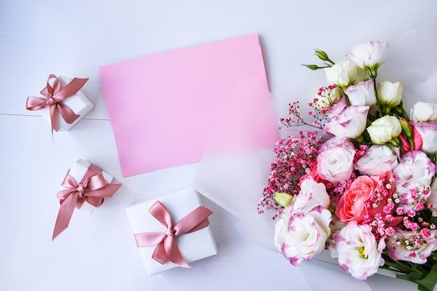Kartenmodell mit zartem blumenstrauß und geschenkboxen. blumenhintergrund. draufsicht flache laien-feiertagskarte 8. märz, glücklicher valentinstag, muttertagskonzept. kopieren sie platz für text. feiertagsgrußkarte