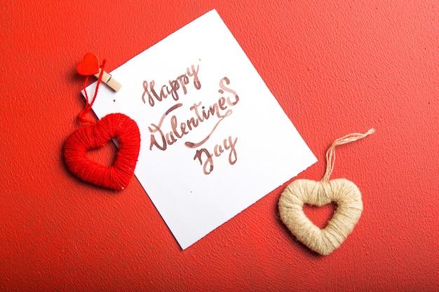 Kartennachricht mit glücklichem valentinstag und herzspielzeug auf rotem tisch