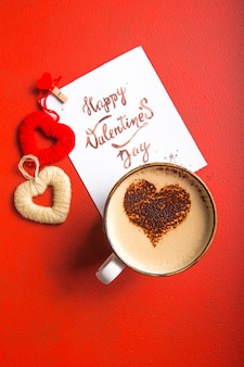 Kartennachricht mit happy valentines day, goldenem besteck, kaffee und herzspielzeug