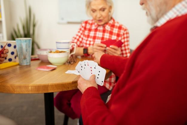 Kartenspiele spielen. verschiedene karten in der hand eines netten, angenehmen älteren mannes