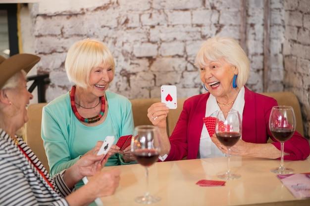 Kartenspielen. ältere fröhliche frauen, die karten spielen und aufgeregt aussehen