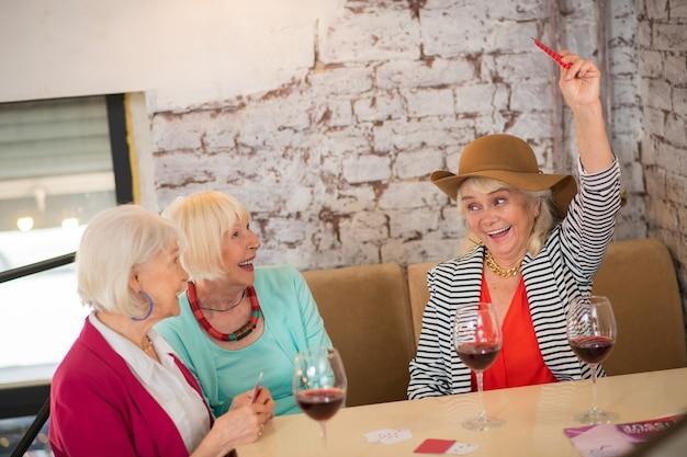 Kartenspielen. ältere gutaussehende fröhliche frauen, die karten spielen und genossen aussehen looking