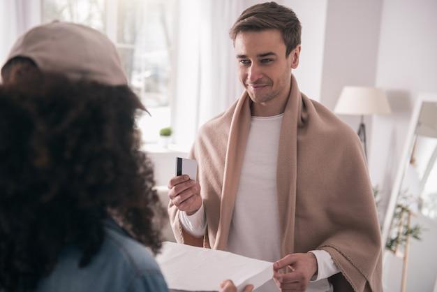 Kartenzahlung. glücklicher gutaussehender mann, der seine bestellung annimmt, während er sie mit karte bezahlt