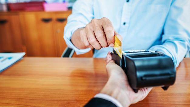 Kartenzahlungen zwischen geschäftsleuten über kreditkartenautomaten im büro.