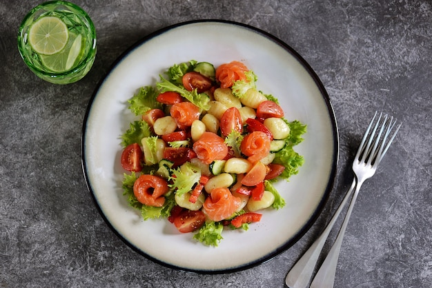 Kartoffel-gnocchi-salat mit tomaten, gurken, paprika, lachs und salat