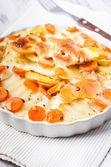 Kartoffel-karotten-gratin mit kräutern in schüssel