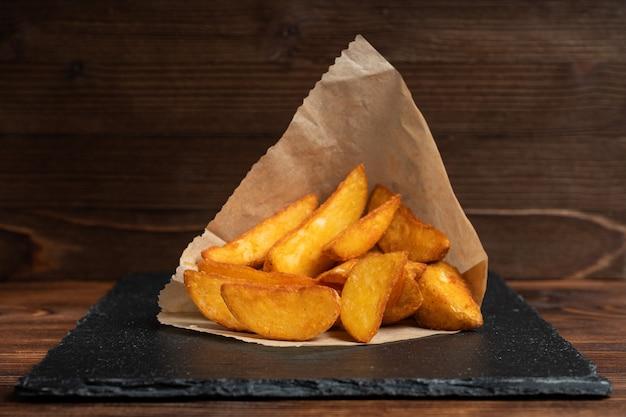 Kartoffel rustikal geschirr schiefer, schwarzer stein auf einem holz nahaufnahme.