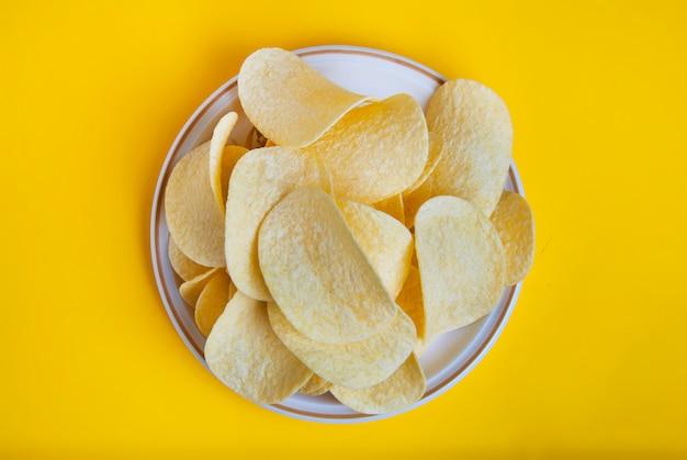 Kartoffelchipnahaufnahme, ungesunder schnellimbiß. gelber hintergrund