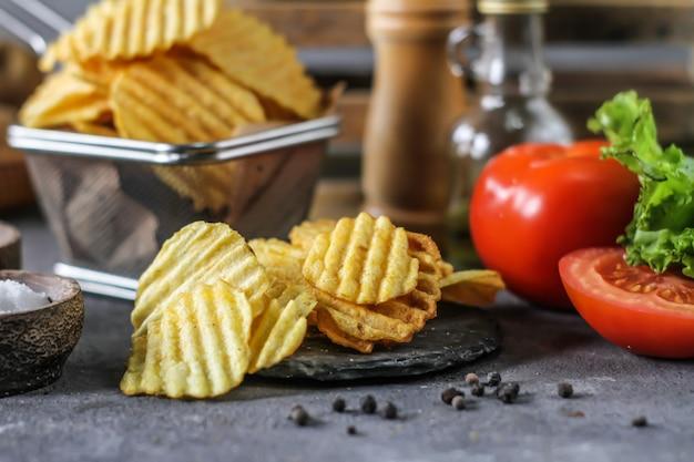 Kartoffelchips auf dem tisch mit zutaten herum