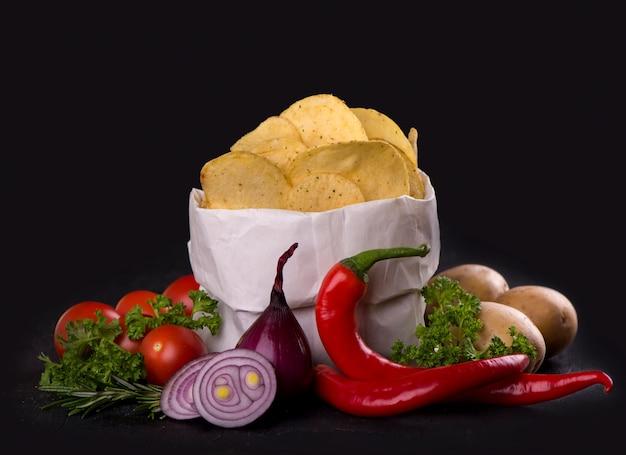 Kartoffelchips auf einem dunklen holzbrett. fast food.