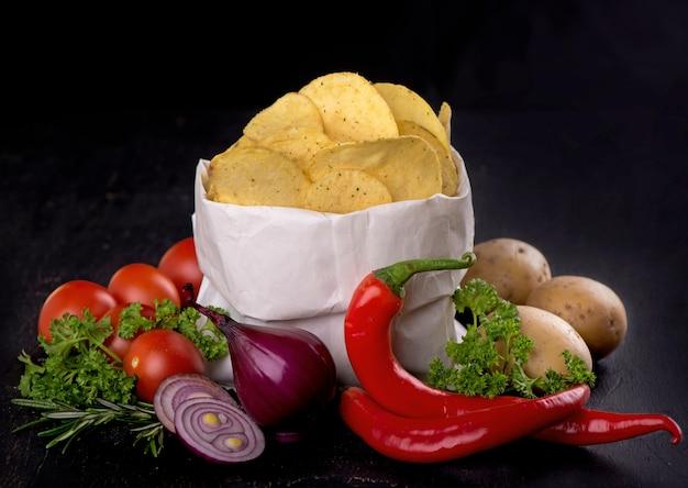 Kartoffelchips auf einem dunklen holzbrett.