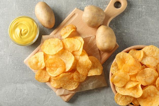 Kartoffelchips. bier snacks, sauce, kartoffel auf schneidebrett, auf grau, platz für text. draufsicht