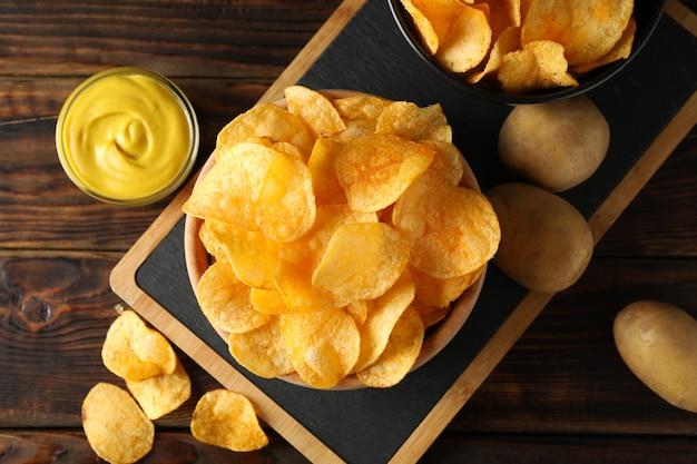 Kartoffelchips. bier snacks, sauce, kartoffel auf schneidebrett, auf holz, platz für text. draufsicht